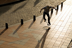 Skateboader jumping on tiled sidwalk and his shadow, Cuenca, Ecuador, South America
