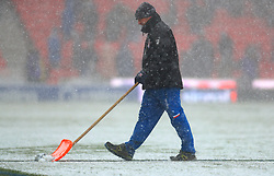 A member of ground staff clears the snow during the Premier League match at the bet365 Stadium, Stoke.