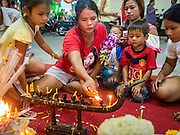 """07 MARCH 2015 - NAKHON CHAI SI, NAKHON PATHOM, THAILAND: A family lights candles to make merit during the Wat Bang Phra tattoo festival. Wat Bang Phra is the best known """"Sak Yant"""" tattoo temple in Thailand. It's located in Nakhon Pathom province, about 40 miles from Bangkok. The tattoos are given with hollow stainless steel needles and are thought to possess magical powers of protection. The tattoos, which are given by Buddhist monks, are popular with soldiers, policeman and gangsters, people who generally live in harm's way. The tattoo must be activated to remain powerful and the annual Wai Khru Ceremony (tattoo festival) at the temple draws thousands of devotees who come to the temple to activate or renew the tattoos. People go into trance like states and then assume the personality of their tattoo, so people with tiger tattoos assume the personality of a tiger, people with monkey tattoos take on the personality of a monkey and so on. In recent years the tattoo festival has become popular with tourists who make the trip to Nakorn Pathom province to see a side of """"exotic"""" Thailand.   PHOTO BY JACK KURTZ"""
