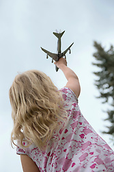 Young blonde girl holding up toy airplane