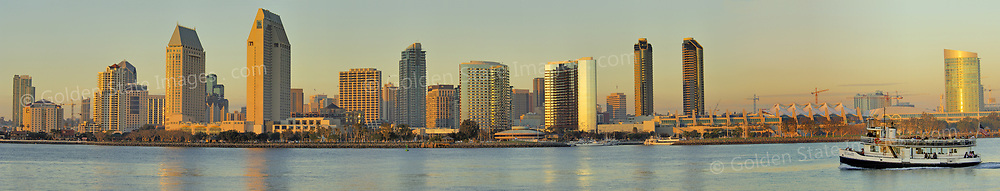 Coronado Ferry heads back across the bay. A setting sun paints the San Diego skyline. Panoramic available up to 14705x2811 pixels.