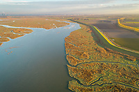 Aerial view of a river passing between wetland ecosystem, Netherlands.