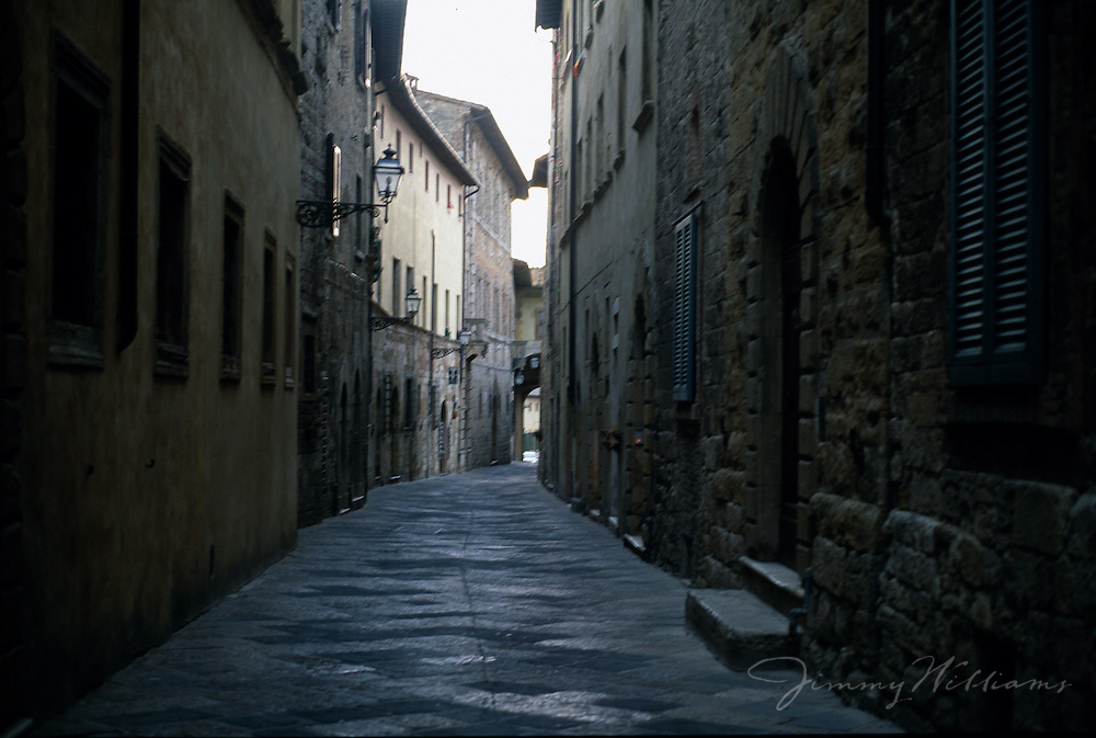 A dark stone alleyway in an old town in Italy