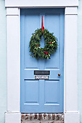 The colorful wooden door on a historic home decorated with a Christmas wreath on Tradd Street in Charleston, SC.