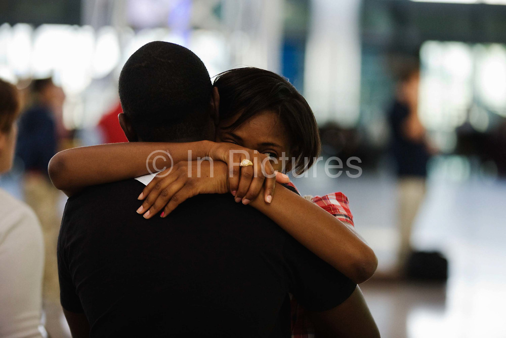 """A departing lover hugs her boyfriend farewell before her long-haul flight in the Departures concourse at. Heathrow Airport's Terminal 5. While embracing her young man, she gazes off into the distance amid the otherwise busy airport terminal where the emotions of parting as well as the joys of reunited loved-ones are played out in various parts of aviation hubs around the world. They are both in their own worlds, removed from the noise and confusion of other passengers. Her departure is brief and yet their sadness of being separated is plainly too much to bear. From writer Alain de Botton's book project """"A Week at the Airport: A Heathrow Diary"""" (2009)."""