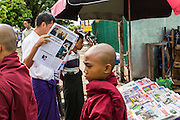 18 JUNE 2013 - YANGON, MYANMAR: A Burmese man reads the newspaper while monks on their morning alms rounds pass him. The Burmese newspaper industry has enjoyed explosive growth this year after private ownership was allowed in 2013. Private newspapers were shut down under former Burmese leader Ne Win in the early 1960s. The revitalized private press is a sign of the dramatic changes sweeping Myanmar, formerly Burma, in the last three years.      PHOTO BY JACK KURTZ