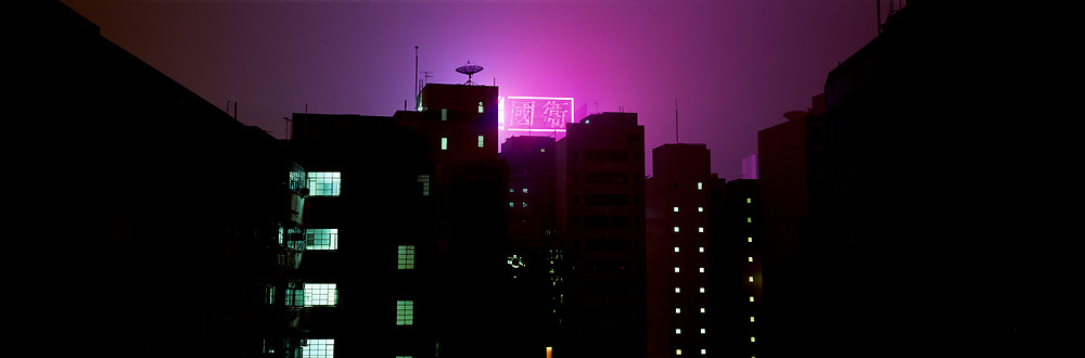 Neon sign at night with buildings and rooftops