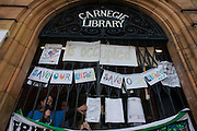 The occupiers of Carnegie Library appear at the building's locked gates in Herne Hill, south London while occupiers remain inside the premises on day 5 of its occupation, 4th April 2016. The angry local community in the south London borough have occupied their important resource for learning and social hub for the weekend. After a long campaign by locals, Lambeth have gone ahead and closed the library's doors for the last time because they say, cuts to their budget mean millions must be saved. A gym will replace the working library and while some of the 20,000 books on shelves will remain, no librarians will be present to administer it.
