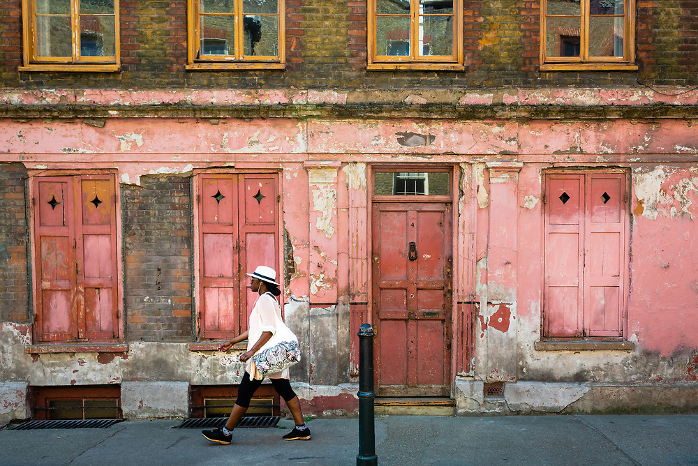 Woman passing old building facade in London's East End