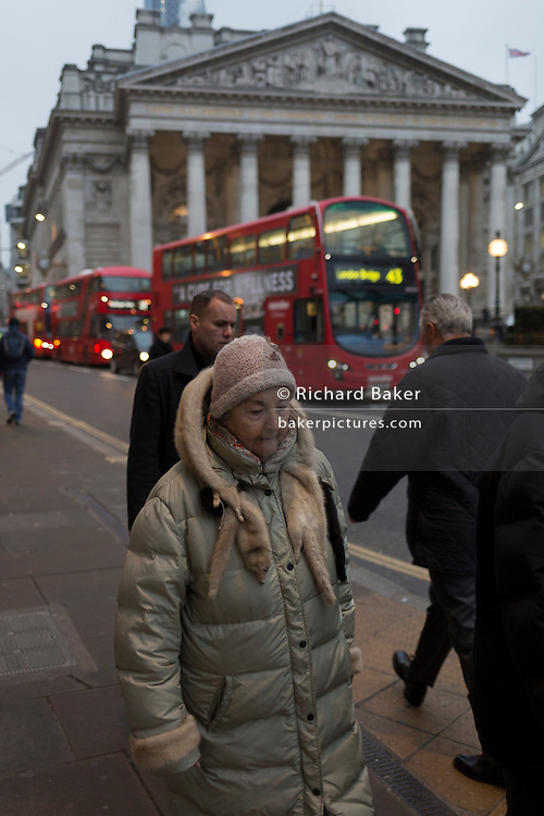 An elderly lady wearing a fur stole of an animal walks through Bank triangle, on 9th February 2017, outside the Bank of England, in the City of London, England.