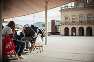 Some African migrants spend the day in the main square.  Irun (Basque Country). October 11, 2018. A group of volunteers has created a host network to serve migrants and inform about the public services they are entitled to and the ways to cross the border. This group of volunteers is avoiding a serious humanitarian problem Irun, the Basque municipality on the border with Hendaye. As the number of migrants arriving on the coasts of southern Spain incresead, more and more migrants are heading north to the border city of Irun. French authorities have reacted by conducting random checks as far as the city of Bordeaux, more than 200 kilometers north of the border. Migrants who are caught are then deported back to Irun. (Gari Garaialde / Bostok Photo).