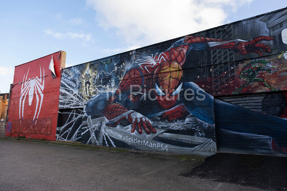 Spiderman street art in the old industrial area and railway arches of Digbeth on 14th December 2020 in Birmingham, United Kingdom. Following the destruction of the Inner Ring Road, Digbeth is now considered a district within Birmingham City Centre, and is the epicentre for arts and graffiti artworks as well as its status as a once-gritty bohemian district known for street art and a young and hip people attending events and creative workshops at the Custard Factory and grungy clubs in former warehouses. As part of the Big City Plan, Digbeth is undergoing a large redevelopment scheme that will regenerate the old industrial buildings into apartments, retail premises, offices and arts facilities. There is still however much industrial activity in the south of the area.