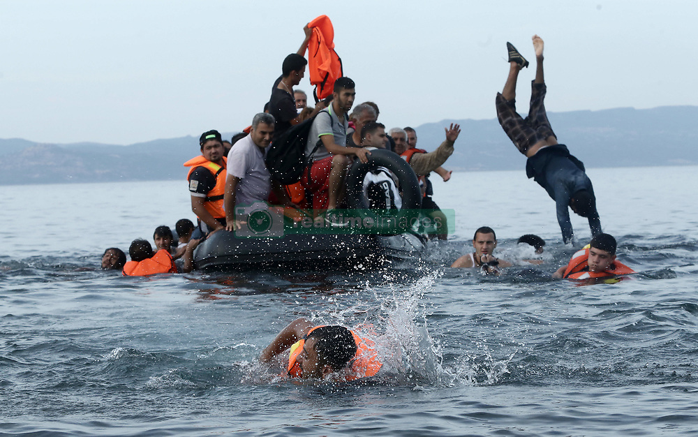 Sept. 9, 2015 - Lesvos, Greece - The press, volunteers from Europe, locals who collect the equipment of the boats, are the first to meet the immigrants from Afghanistan, Iraq, Bangladesh and also the Syrian refugees who are the majority of the people to arrive on the east coast of Lesbos island, with small boats having cross the Aegean sea from the western coast of Turkey. Lesbos island, Greece, on Wednesday, September 9, 2015. (Credit Image: © Panayiotis Tzamaros/NurPhoto via ZUMA Press)