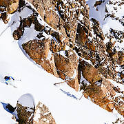 Tanner Flanagan skis powder covered rocks in the backcountry near Jackson Hole Mountain Resort.