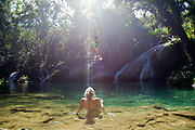 Young woman reclining relaxing in fresh water, El Nicho, in the forest between Ciengfuegos and Trinidade, Cienfuegos province, Cuba. .
