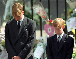 Prince William (left) and Prince Harry, the sons of Diana, Princess of Wales, bow their heads as their mother's coffin is taken out of Westminster Abbey following her funeral service. The princess was killed in a car crash in Paris.