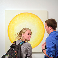Madison Sutliff, left, tosses her hair as she and Logan Hangle view a painting of the sun from artist Patrick Kikut at the University of New Mexico in Gallup Monday.