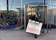 © Licensed to London News Pictures. 04/12/2012. London, UK Lauren Tinney from the GMB union holds a placard awarding Starbucks an 'ASBO for antisocial behaviour' after being prevented from handing it in to the headquarters reception. GMB union members demonstrate outside Starbucks Head Quarters on Chiswick High Road, London, over complaints that the coffee firm does not pay its staff the Living Wage, today 4th December 2012. Photo credit : Stephen Simpson/LNP
