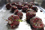Garnished and seasoned raw meatballs before cooking set out on a tray