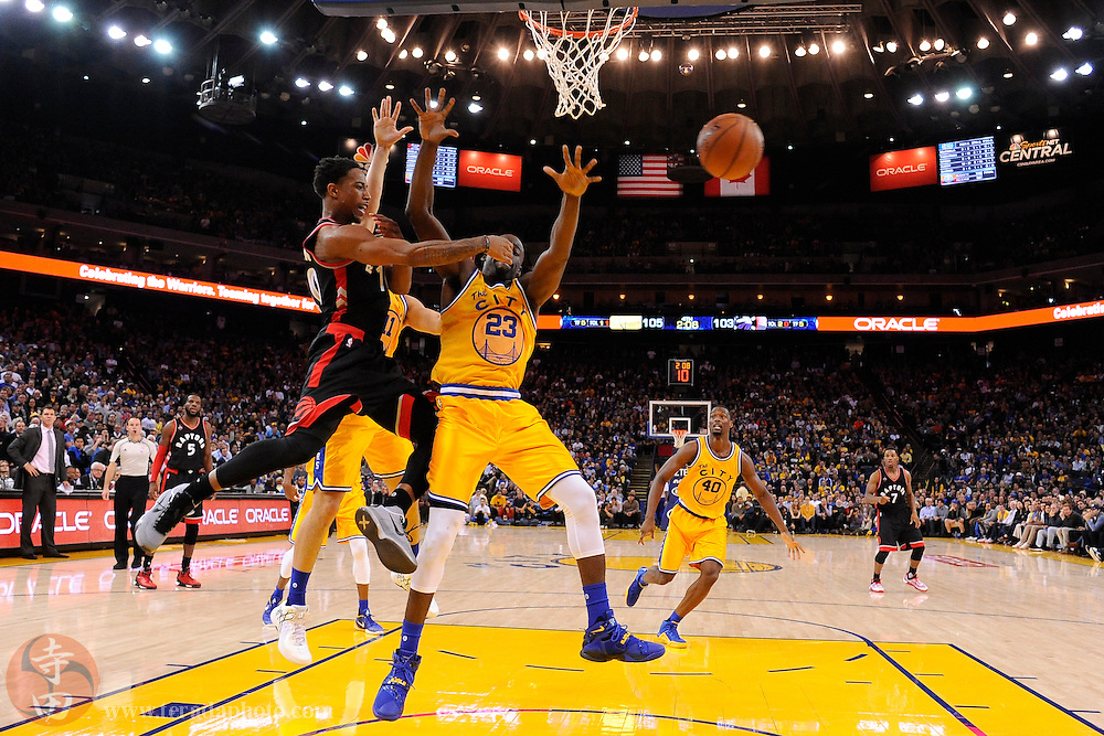 November 17, 2015; Oakland, CA, USA; Toronto Raptors guard DeMar DeRozan (10) passes the basketball against Golden State Warriors forward Draymond Green (23) during the fourth quarter at Oracle Arena. The Warriors defeated the Raptors 115-110.