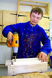 Young man with Downs Syndrome learning how to use drill at a workshop for craftspeople with learning disabilities UK