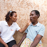 CAPTION: This is Honorine, who represents Smile Train in Rwanda. She has come to know Theresia very well. For a while after first hearing from Honorine that she could get her cleft repaired, Theresia could not see the point of the operation being done. After all, she had lived with the condition for 73 years and felt used to living life that way. However, President Kagame was known to have talked of his determination for a Rwanda free of all repairable birth defects. Someone told Theresia about the President's declaration, and suggested to her that if she didn't take up the offer of surgery then she would be letting him down. Deciding to go ahead with the operation was, she says, a patriotic decision. For her part, Honorine was delighted that Theresia had changed her mind, and assured her that she would be there to support her every step of the way. LOCATION: Rutare, Byumba-Gichumbi, Rwanda. INDIVIDUAL(S) PHOTOGRAPHED: Honorine Namukara (left) and Theresia Nzabamwita (right).