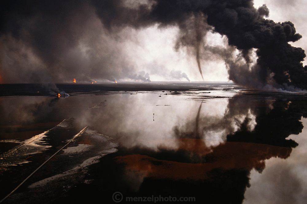A tornado of oil and smoke is mirrored in a vast lake of oil in the Al-Burgan Oil Fields, Kuwait. In this field alone, there were more than 300 oil wells set ablaze by retreating Iraqi troops in the largest man-made environmental disaster in history. The $20 billion effort to extinguish the fires lasted until the end of the year. Each day, in this oil field alone, the loss was estimated at 5 to 6 million barrel. Huge burning oil lakes added smoke and oily rain to a nightmarish scene. May, 1991. (NPPA Winner; Communication Arts Winner).