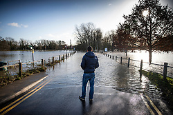 © Licensed to London News Pictures. 23/12/2019. Yalding, UK. A man looks as flood water on the road near Yalding in Kent. River levels are slowly beginning to drop after days of heavy rain in the south. Photo credit: Peter Macdiarmid/LNP