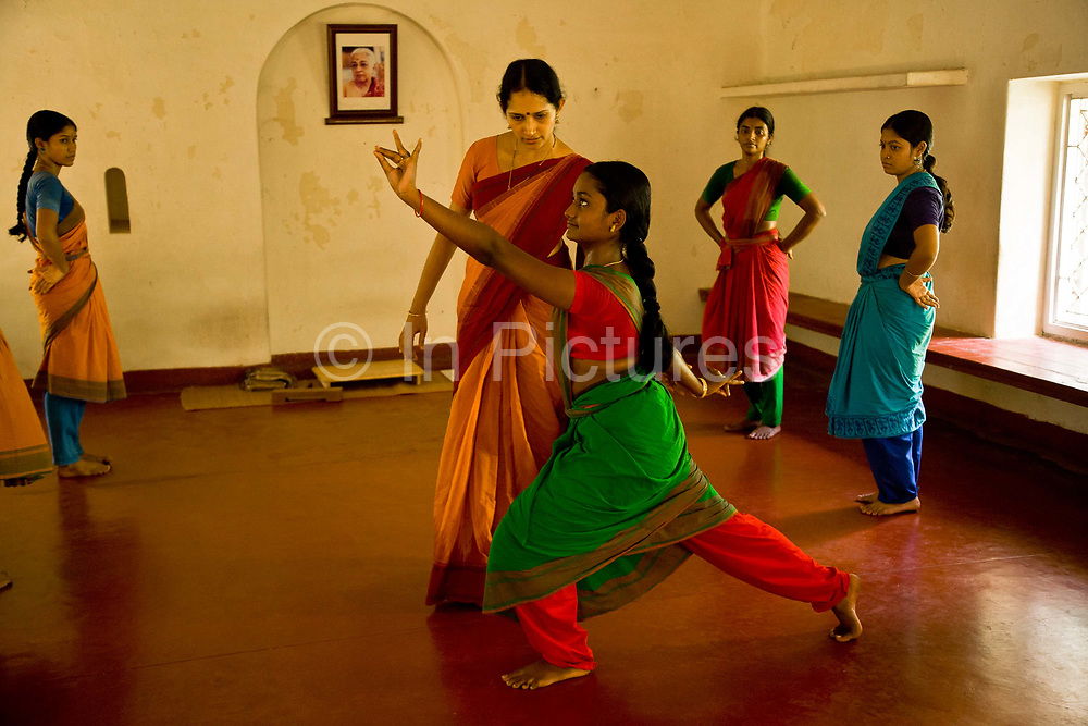 """Ganga Thampi, teaches young  trainee dancers  movement, rhythm and expression, known as nritya at the traditional and highly prestigious Kalakshetra school for the arts, Chennai. The school was founded in 1936 and due to its exacting and demanding schedule is considered India's formost classical dance academy of this ancient cultural art heritage that is informally known as """"temple dancing"""" and that dates back to the Natya Shastra, the 2000 year old text that lays down the principles of Indian dramatic theory and performance. Tamil Nadu, India."""