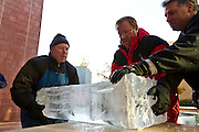 Taking special care not to drop the final piece of the tree-shaped, 8' tall beverage luge, Bill Gordish, Grinnell College Executive Chef Scott Turley, and Jim Nadeau (left to right) gently place the heavy block of ice onto a nearby table.