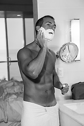 hot Latin man in a towel putting on shaving cream