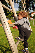young child of two climbs up a ladder in a playground Photographed in Austria