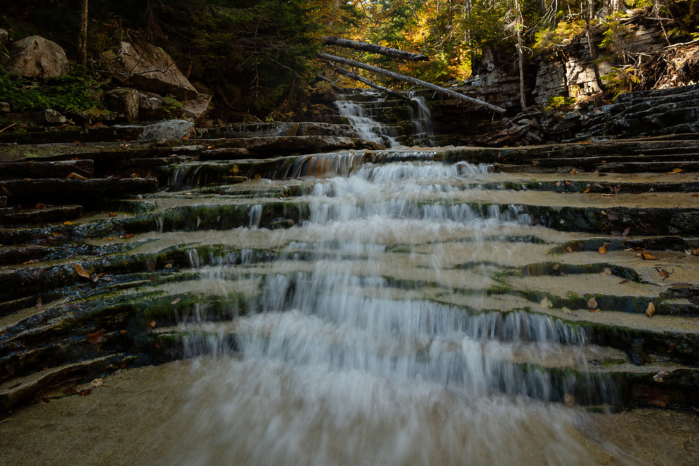 Mountain water sliding down the face of Coliseum Falls on a warm autumn afternoon in the forests of New Hampshire.