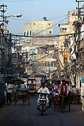 A rickshaw wallah cycles through a street in Old Delhi, India.