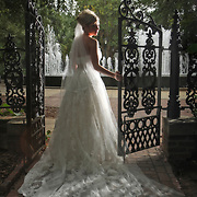 A bride poses for her bridal portrait on the South Carolina Governor's Mansion grounds while standing near the gates and water fountain beside The Lace House in Columbia. Photo by Columbia SC wedding photographer Travis Bell.   ©Travis Bell Photography