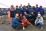 Firefighters from the KWWK (Kuwait Wild Well Killers) pose for group picture at Rumaila Oil Field in southern Iraq. The Rumaila field is one of Iraq's biggest oil fields with five billion barrels in reserve. Many of the wells are 10,000 feet deep and produce huge volumes of oil and gas under tremendous pressure, which makes capping them very difficult and dangerous. This well was of relatively low volume. Rumaila is also spelled Rumeilah.