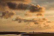 A fishermen walks along the beach at dawn on Isle of Palms at Wild Dunes near Charleston, South Carolina.