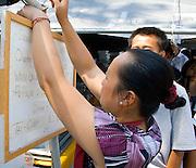 Hmong woman hanging menu on front of outdoor restaurant. Hmong Sports Festival McMurray Field St Paul Minnesota USA