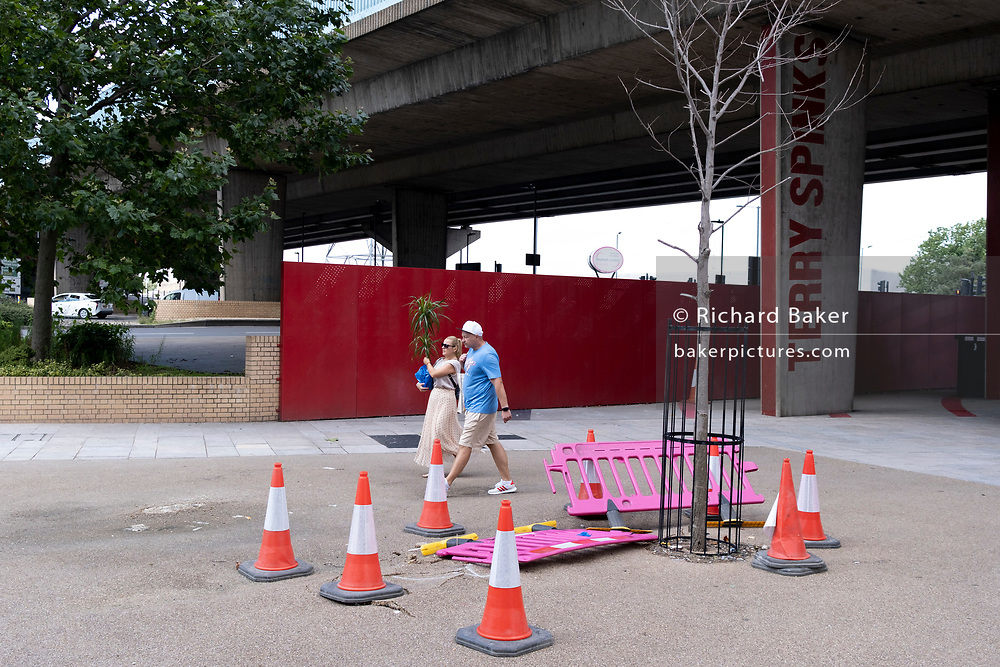 A woman carries a new pot plant past a dead tree at the underpass of the A13 Newham Way, at Canning Town in the East End, on 11th August 2021, in London, England.