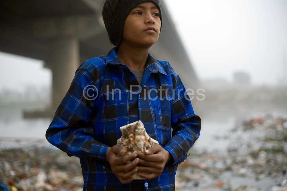A young ragpicker and a discardrd statue of Ganesh that have been ritually submerged into the Yamuna. The river, by the Kudsia Ghat in Delhi is so polluted that it can no longer support life, however a community still live and work on it's banks. The boy, like many works as a scavenger, searching for anything valuable to sell