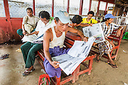 17 JUNE 2013 - YANGON, MYANMAR: Men read newspapers in the waiting room at the Dala ferry terminal for the Yangon-Dala ferry. The Burmese newspaper industry has enjoyed explosive growth this year after private ownership was allowed in 2013. Private newspapers were shut down under former Burmese leader Ne Win in the early 1960s. The revitalized private press is a sign of the dramatic changes sweeping Myanmar, formerly Burma, in the last three years.      PHOTO BY JACK KURTZ