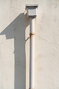 rainwater drainpipe with shadow at residential building