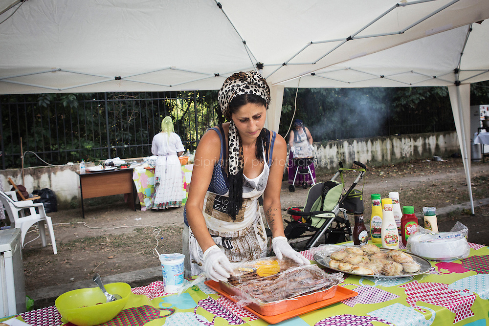 """ROME, ITALY - 3 JULY 2016: Gipsy Queen member Aninfa Hokic (31) serves a customer at a food stand at the iFest, an alternative music festival  in Rome, Italy, on July 3rd 2016.<br /> <br /> The Gipsy Queens are a travelling catering business founded by Roma women in Rome.<br /> <br /> In 2015 Arci Solidarietà, an independent association for the promotion of social development, launched the """"Tavolo delle donne rom"""" (Round table of Roma women) to both incentivise the process of integration of Roma in the city of Rome and to strengthen the Roma women's self-esteem in the context of a culture tied to patriarchal models. The """"Gipsy Queens"""" project was founded by ten Roma women in July 2015 after an event organised together with Arci Solidarietà in the Candoni Roma camp in the Magliana, a neighbourhood in the South-West periphery of Rome, during which people were invited to dance and eat Roma cuisine. The goal of the Gipsy Queen travelling catering business is to support equal opportunities and female entrepreneurship among Roma women, who are often relegated to the roles of wives and mothers."""