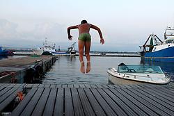 Bambino si tuffa nelle acque del porto di Taranto.