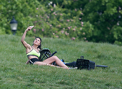 © Licensed to London News Pictures. 07/05/2020. London, UK. A woman takes a selfie while sitting on Primrose Hill in London in the warm weather. Government is set to announce measures to easy lockdown, which was introduced to fight the spread of the COVID-19 strain of coronavirus.. Photo credit: Ben Cawthra/LNP