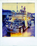 Two boys sit on top of a decorated Jeepney, a vehicle originally made from recycled U.S. World War II military jeeps, and used today as a popular form of public transportation, Palawan Island, Philippines, Southeast Asia