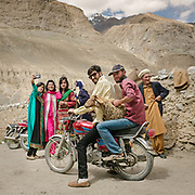 Women doing selfies while men are bringing a sheep on their motorcyle.