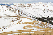A hiker ascends the broad ridge to Grizzly Peak near Loveland Pass, Rocky Mountains, Colorado.