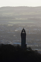 The Wallace Monument tower standing on the summit of Abbey Craig, a hilltop near Stirling in Scotland. View from the slope of the Dumyat, a hill at the western extremity of the Ochil Hills, in central Scotland..Pic © Michael Schofield...