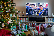 Christmas presents remain unopened beneath a Christmas tree and footage of Prince Charles meeting members of the military during the Queen's speech to the nation on Christmas Day, a tradition started in 1932 and which she first broadcast on television in 1957, on 25th December 2019, in Bristol, England.